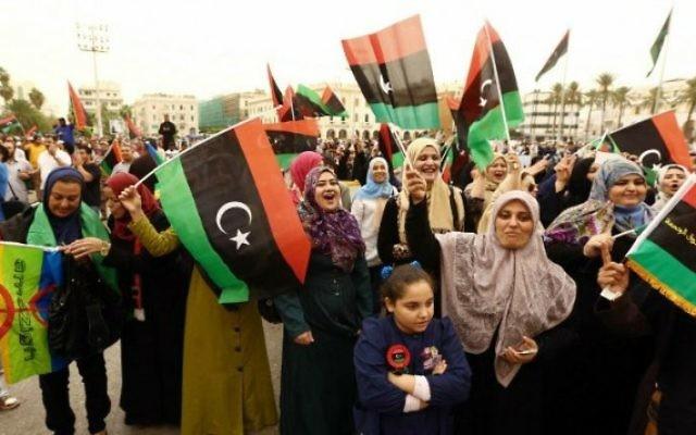 Des Libyens avec leur drapeau sur une place de Tripoli, le 6 novembre 2014. (Crédit : Mahmud Turkia/ AFP)