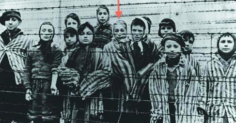 Marta Wise (au centre, sous la flèche rouge) avec un groupe d'enfants derrière les barbelés d'Auschwitz. (autorisation)