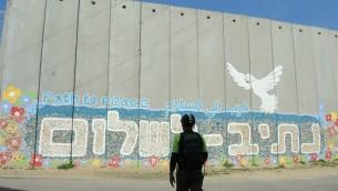 Patricio (Pato) Tanner devant le mur du village de Netiv Haassara, où les visiteurs peuvent ajouter leur morceau de poterie sur le mur. (Crédit : Melanie Lidman/Times of Israel)