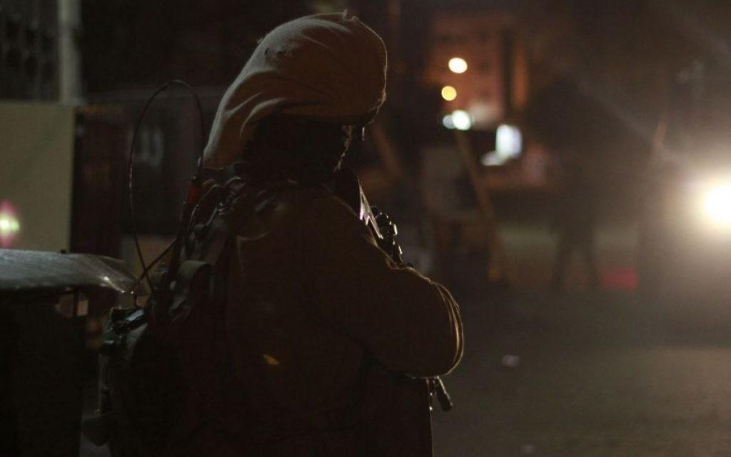 Un soldat de garde sous la lumière de la jeep de l'armée à Qalqilya le 14 janvier 2016. Les véhicules que l'armée utilise pendant ces raids nocturnes sont tous blindés contre les balles, les pierres et les cocktails Molotov. (Crédit : Judah Ari Gross/Times of Israel)