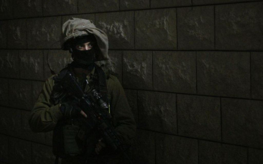 Un soldat se prépare à entrer dans la maison d'un adolescent palestinien, suspecté d'avoir jeter des pierres sur des soldats israéliens pendant une émeute à Qalqilya. Une équipe était déjà entrée dans la maison pour réveiller la famille, qui avait initialement affirmé que son fils n'était pas à la maison, le 14 janvier 2016. (Crédit : Judah Ari Gross/Times of Israel)