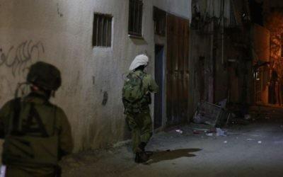 Des soldats de l'armée israélienne avancent vers la maison de deux adolescents palestiniens suspectés d'avoir pris part à de violentes manifestations à Qalqilya. Un représentant arabophone du coordinateur des activités gouvernementales dans les Territoires accompagne le bataillon pour faciliter la conversation entre les soldats et les familles des accusés, le 14 janvier 2016. (Crédit : Judah Ari Gross/Times of Israel)