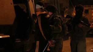Des soldats embarquent l'un des suspects à l'arrière d'un Zeev, un grand véhicule blindé de transport de personnes, à Qalqilya le 14 janvier 2016. Le commandant des soldats, Lt. Col. Nimrod Cibulski, leur a fait éloigner l'adolescent palestinien de sa famille avant de lui attacher les mains et de lui bander les yeux, afin d'épargner au père du suspect la vision de son fils attaché, selon Cibulski. (Crédit : Judah Ari Gross/Times of Israel)