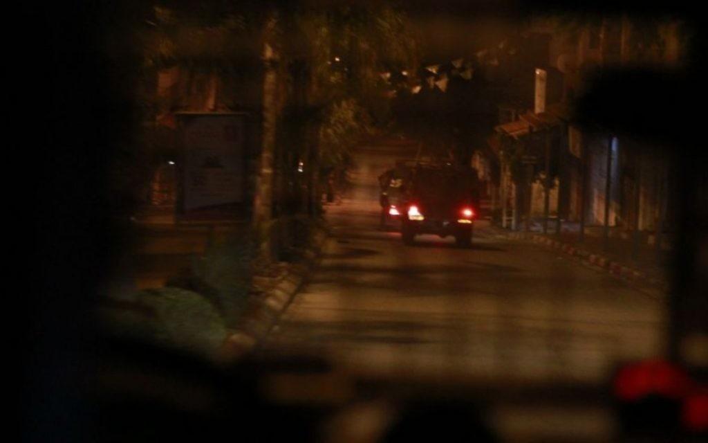 Une jeep de l'armée israélienne à Qalqilya le 14 janvier 2016. Alors que le véhicule militaire quitte la ville, certains résidents lui jettent des pierres, sans causer aucun dommage. Les trois suspects arrêtés par le bataillon Tigre seront remis aux forces de l'ordre plus tard ce matin-là. (Crédit : Judah Ari Gross/Times of Israel)