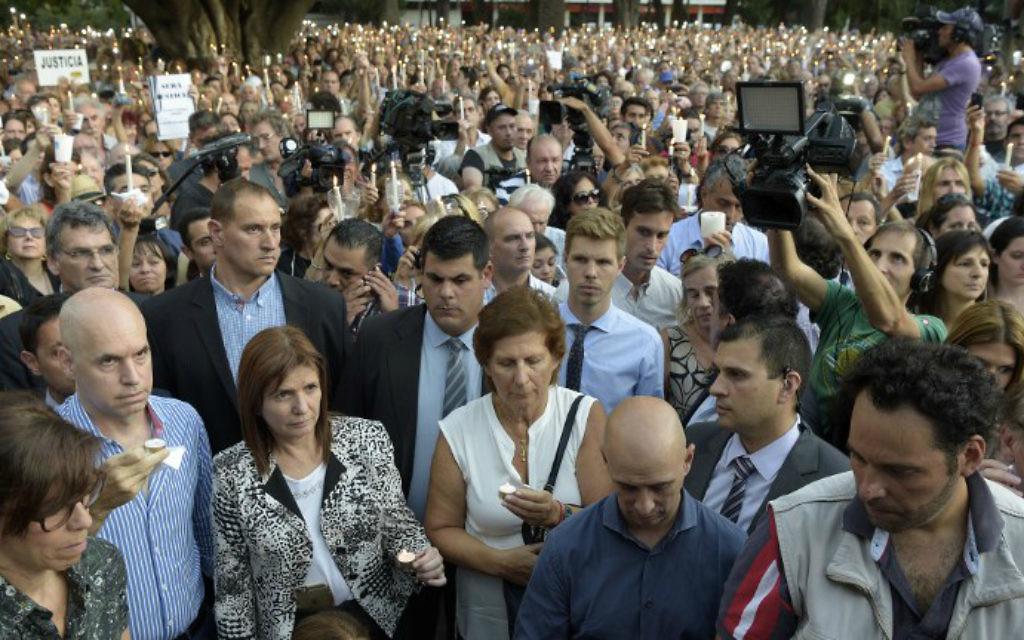La foule se rassemble autour de Sara Garfunkel (au centre), la mère du procureur argentin Alberto Nisman, pendant une veillée aux chandelles pour le premier anniversaire de la mort mystérieuse de son fils, à Buenos AIres, le 18 janvier 2016. (Crédit : AFP Photo/Eitan Abramovich)