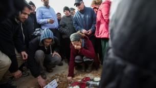 Les personnes en deuil sur la tombe de Dafna Meir, pendant ses funérailles à Jérusalem le 18 janvier 2016. (Crédit : Yonatan Sindel/Flash90)