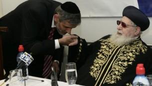 L'ancien ministre de l'Intérieur, Eli Yishai, embrasse la main du défunt leader spirituel du parti ultra-orthodoxe Shas Ovadia Yosef au cours de la cérémonie d'inauguration du nouveau siège du Collège Haredi à Jérusalem le 14 décembre 2009 (Crédit photo: Abir Sultan / Flash90)