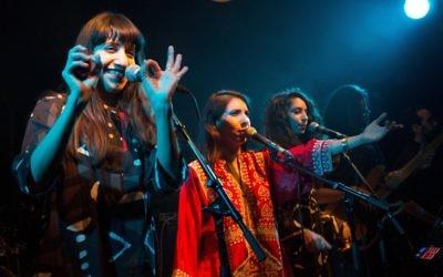 """Les sœurs israéliennes Tair (au centre) 31 ans, Liron (à gauche) 29 ans et Tagel (à droite) 25 ans, les membres du groupe folk A-WA, (prononcé """"Aywa,"""" ou oui en arabe), lors d'un spectacle à Jérusalem, le 28 janvier 2016 (Crédit : AFP / MENAHEM KAHANA)"""