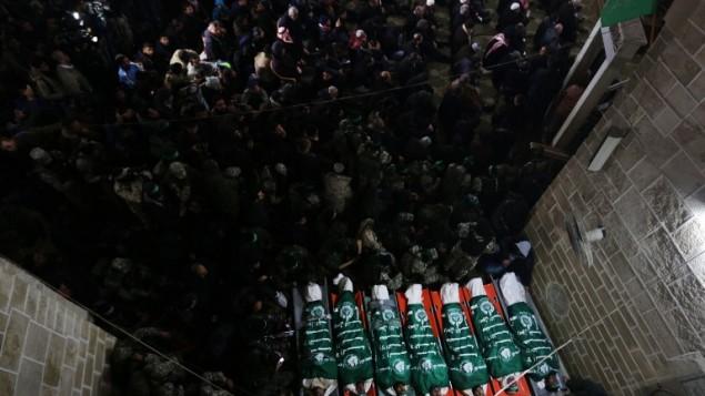 Des combattants du Hamas se rassemblent autour des corps de sept ouvriers tués dans l'effondrement d'un tunnel dans la bande de Gaza, pendant leurs funérailles, le 29 janvier 2016. (Crédit : AFP/Mahmud Hams)