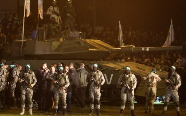 Des membres palestiniens de la branche armée du Hamas rassemblés autour d'un faux char israélien le 31 janvier 2016, en hommage aux Gazaouis morts dans l'effondrement d'un tunnel. (Crédit : AFP / MAHMUD HAMS)