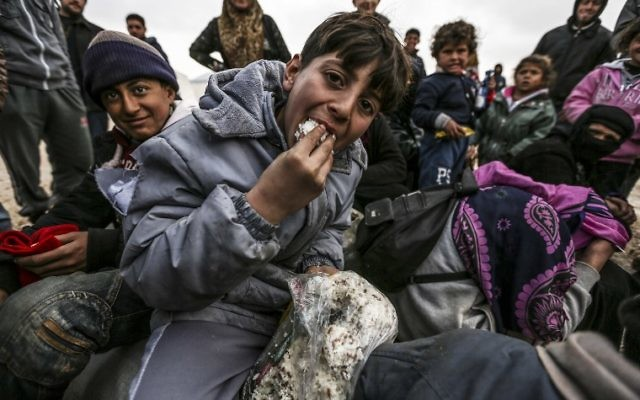 Des réfugiés syriens qui ont fuit la ville assiégée d'Alep attendent à Bab al-Salama, dans le nord de la Syrie, près de la frontière turque, le 6 février 2016. (Crédit : AFP/Bulent Kilic)