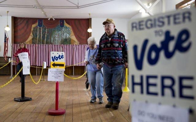Un homme et une femme américains viennent de voter à Chichester, New Hampshire. le 9 février 2016 (Crédit : DOMINICK REUTER / AFP)
