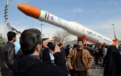 Des Iraniens prennent des photos d'une réplique de la fusée Simorgh, capable de lancer des satellites, pendant les célébrations du 37ème anniversaire de la République islamique, à Téhéran, le 11 février 2016. (Crédit : AFP/Atta Kenare)
