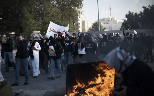 Des manifestants bahreïnites qui prennent part à une manifestation pour marquer le cinquième anniversaire du soulèvement du Printemps arabe qui a eu lieu le 12 février, 2015, dans le village à majorité chiite de Sitra, au sud de Manama (Crédit : AFP / MOHAMMED AL-SHAIKH)