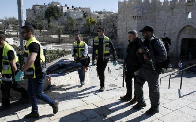 Des bénévoles juifs de Zaka enlèvent le corps d'un Palestinien qui a été abattu après avoir poignarder trois personnes devant la porte de Damas de Jérusalem le 19 février 2016. (Crédit : AFP / THOMAS COEX)