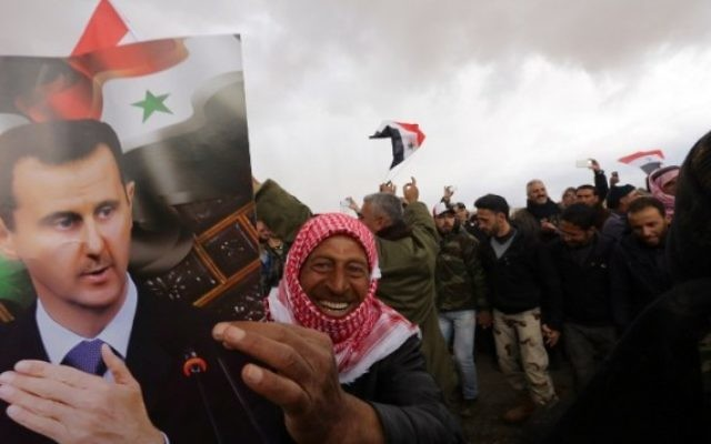 Un volontaire syrien et ses proches brandissent le drapeau national et des portraits du président Bashar el-Assad en célébrant la fin d'un entraînement paramilitaire mené par l'armée syrienne le 22 février 2016. (Crédit : AFP / LOUAI BESHARA)