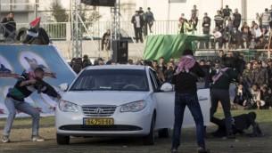 Des Palestiniens simulent une attaque contre une voiture israélienne pendant un spectacle à l'occasion d'un rassemblement anti-Israël à Rafah, dans le sud de la bande de Gaza, le 26 février 2016. (Crédit : AFP / SAID KHATIB)