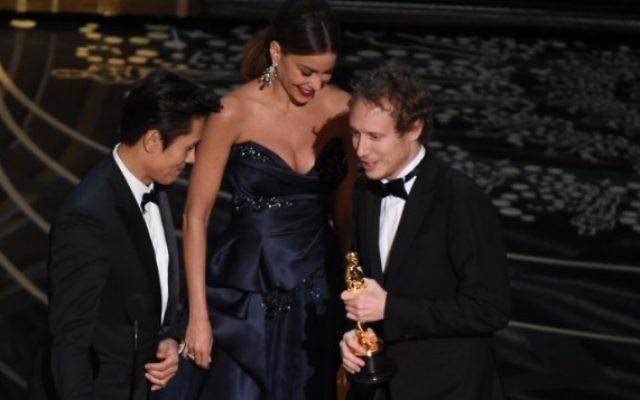 Sofia Vergara et Byung-hun Lee présentent l'Oscar du Meilleur film étranger, Son of Saul, au cinéaste Laszlo Nemes (D) lors de la 88e cérémonie des Oscars, le 28 février 2016 à Hollywood, California. (Crédit : AFP PHOTO / MARK RALSTON)