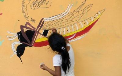 Une jeune fille peint une fresque qui éduque les gens sur un projet de lutte contre les moustiques dans le village de San Diego, à La Libertad, Salvador, le 4 février 2016 (Crédit : AFP PHOTO / MARVIN RECINOS)