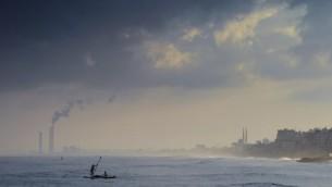 Pêcheurs palestiniens pagayant sur leur petit bateau à quelques centaines de mètres de la plage de Gaza ville, tout en lançant leurs filets à la recherche de petits poissons, le 10 août 2014. (Crédit : AFP/Roberto Schmidt)