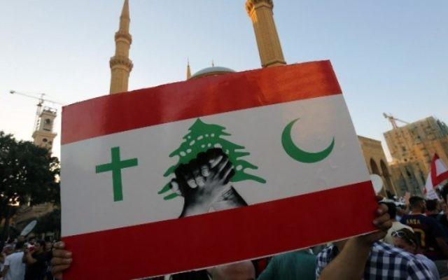 Un manifestant libanais brandit un panneau pendant un rassemblement de masse contre la classe politique perçue comme corrompue et incapable de fournir les services élémentaires, sur l'iconique place des Martyrs de Beyrouth, le 29 août 2015. (Crédit : AFP PHOTO / STR)