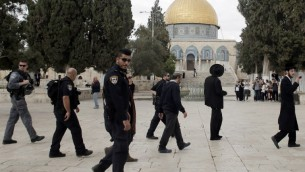 Des Juifs religieux sous la protection de la police israélienne lors d'une visite au mont du Temple dans la vieille ville de Jérusalem, le 27 octobre 2015. (Crédit : Ahmad Gharabli/AFP)