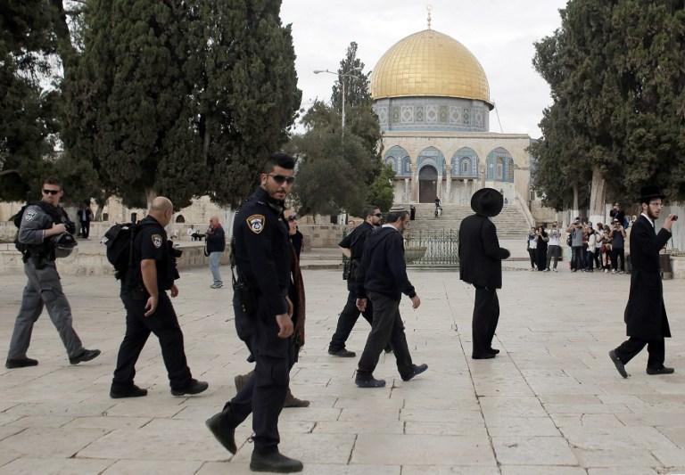 Des hommes juifs ultra-orthodoxes se joingnant à un groupe de juifs religieux sous la protection de la police israélienne lors d'une visite au mont du Temple dans la vieille ville de Jérusalem, le 27 octobre 2015 (Crédit : AFP PHOTO / AHMAD GHARABLI)