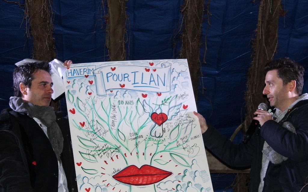 Laurent Barilan-Pariente, président du collectif Haverim, et Philippe Elie Kassabi, artiste, qui tiennent une œuvre signée par les intervenants de la commémoration du 11 février et qui sera prochainement mise aux enchères (Crédit : Times of Israël Staff/Glenn Cloarec)