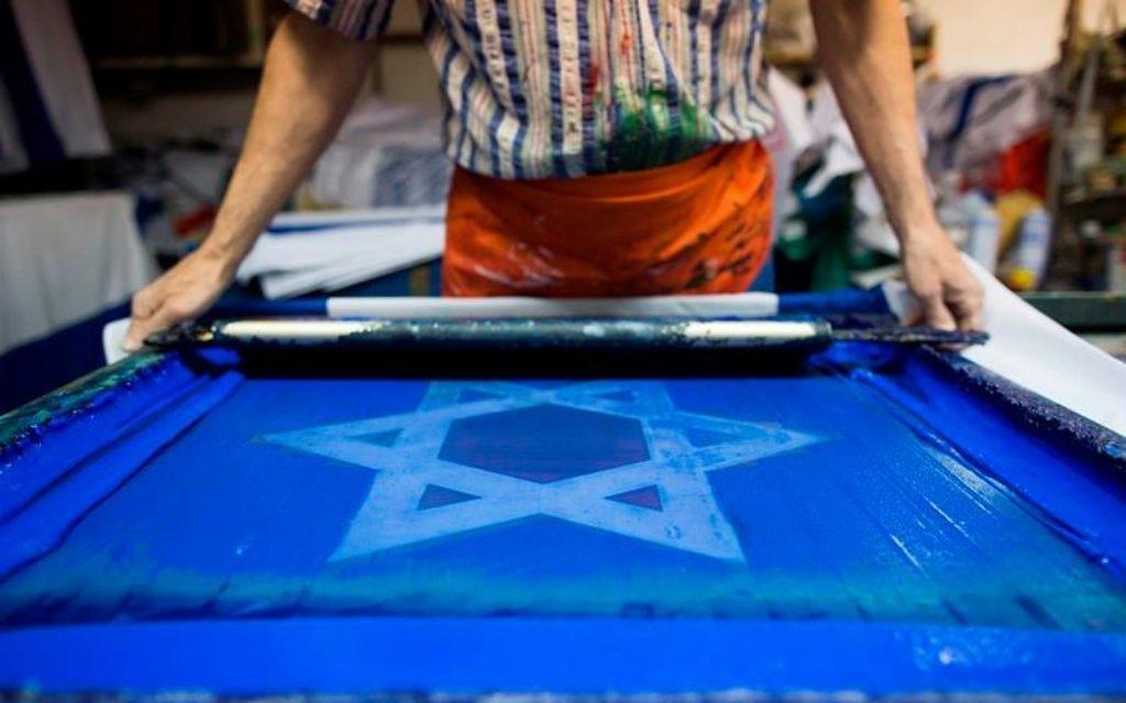 Un artisan qui fabrique un drapeau israélien (Crédit : Flash 90)