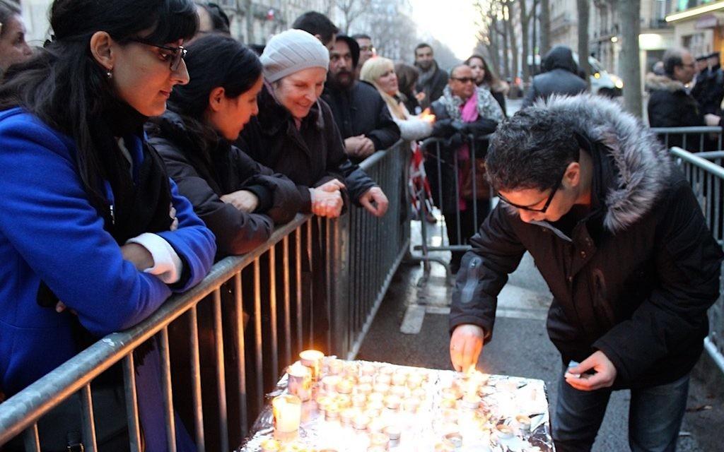 Parmi les participants à la manifestation de ce dimanche 14 février, au 229 boulevard Voltaire, certains agitaient des drapeaux israéliens et d'autres, plus nombreux, tenaient une bougie (Crédit : Times of Israël Staff/Glenn Cloarec)