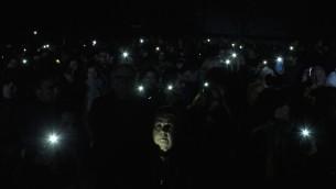 La commémoration de jeudi s'est terminée par la lecture du kaddish, puis par l'allumage symbolique des flashs des téléphones portables – l'utilisation de bougies avait été interdite pour «raisons de sécurité» (Crédit : Times of Israël Staff/Glenn Cloarec)