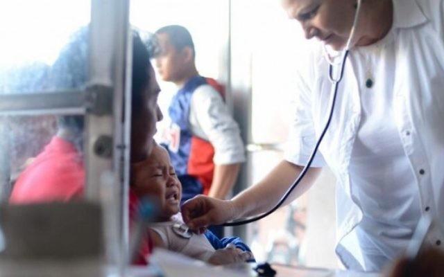 Des membres de l'équipe médicale d'IsraAID soignent les personnes touchés par le typhon. (Crédit : IsraAID/Nufar Tagar)