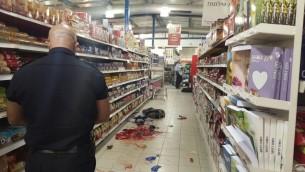 Un policier israélien rassemble des preuves sur les lieux d'une attaque au couteau dans un supermarché dans le parc industriel de Shaar Binyamin, au nord de Jérusalem, le 18 février 2016 (Crédit : Police israélienne)