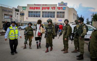 Des soldats israéliens en dehors d'un supermarché Rami Levy au gush Etzion en Cisjordanie, où un terroriste palestinien a blessé une femme israélienne le 28 octobre 2015 (Crédit : Gershon Elinson / Flash90)