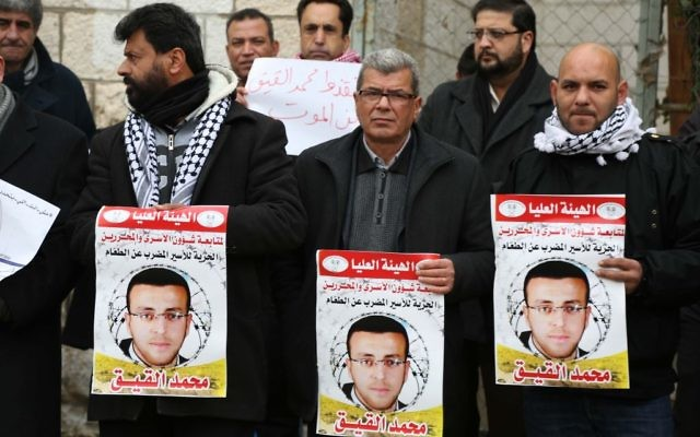 Des militants palestiniens avec des affiches pendant une manifestation pour la libération du journaliste palestinien Mohammed al-Qiq devant le siège de la Croix rouge de Ramallah, en Cisjordanie, le 27 janvier 2016. (Crédit : Flash90)