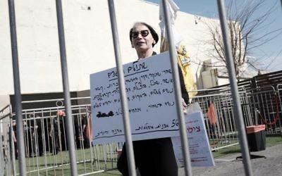 Une femme tient une pancarte contre le rassemblement des ONG de gauche dans le port de Tel Aviv le 5 février 2016. (Crédit : Tomer Neuberg / Flash90