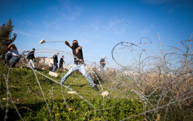 Palestinienne utilisant une fronde à lancer des pierres vers des soldats israéliens (hors du champ) lors d'affrontements près de la ville cisjordanienne de Ramallah, le 12 février 2016 (Crédit : Flash90)