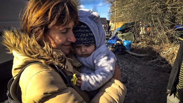 Une femme et son enfant dans un camp de réfugiés dans le nord de la France, en février 2016. (Crédit : IsraAID)