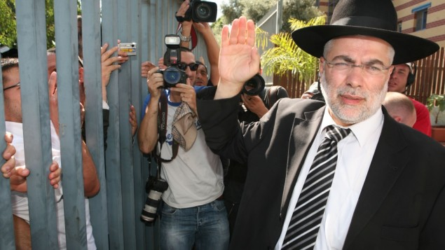 L'ancien député Shlomo Benizri (Shas) salue ses soutiens avant à l'entrée de la prison. Benizri a été condamné à 4 ans de prison pour avoir accepté des pots-de-vin du propriétaire d'une agence de placement. (Crédit : Liron Almog / FLASH90)