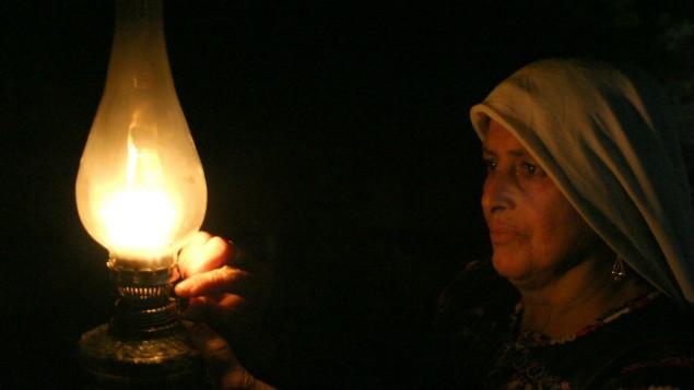 Une femme bédouine palestinienne de la tribu Ghwain allume une bougie dans sa maison du sud de Hébron, le 29 mai 2008. (Crédit : Najeh Hashlamoun /Flash90)
