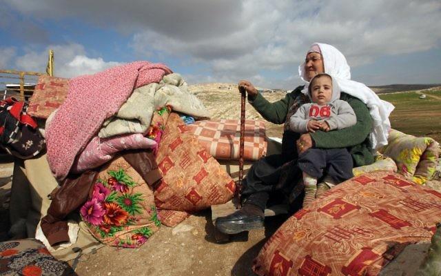 Une femme palestinienne assise avec un enfant à côté de ce qu'ils ont pu récupérer des restes de leur maison après elle a été démolie par les bulldozers israéliens dans la zone militaire de Musafir Jenbach, qui comprend plusieurs villages, au sud de la ville cisjordanienne de Hébron, le 2 février 2016 (Crédit : AFP / HAZEM BADER)