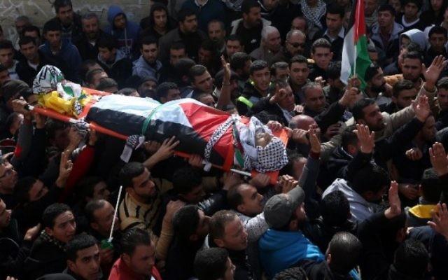 Des Palestiniens portent le corps d'Amjad Abu Omar Sakari, qui a été abattu pendant qu'il menait une attaque contre des soldats israéliens près de l'implantation de Beit El, pendant ses funérailles à Jamain, un village du sud de Naplouse, le 1er février 2016. (Crédit : AFP / JAAFAR ASHTIYEH)