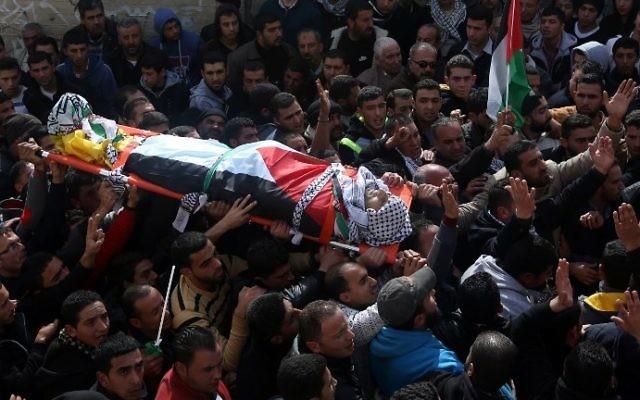 Des Palestiniens en deuil portant le corps d'Amjad Abu Omar Sakari, qui a été abattu en menant une attaque contre des soldats israéliens près de l'implantation de Beit El, lors de ses funérailles dans le village de Jermaine au sud de Naplouse, le 1er Février 2016 (Crédit : AFP / JAAFAR ASHTIYEH)