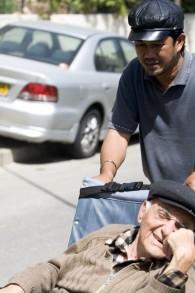 Un Philippin prend soin d'un Israélien âgé en fauteuil roulant. (Photo d'illustration, crédit : Abir Sultan/Flash90)