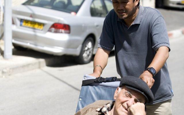 Un Philippin prend soin d'un Israélien en fauteuil roulant. Illustration. (Crédit : Abir Sultan/Flash90)