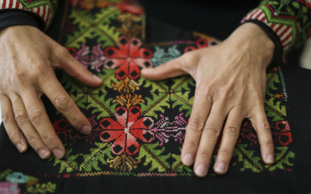 """Une femme bédouine montre l'objet créé par une femme de """"Broderie du désert : association pour l'amélioration pour les femmes"""" dans la ville bédouine de Lakiya, le 1er avril 2014. (Crédit : Hadas Parush/Flash 90)"""
