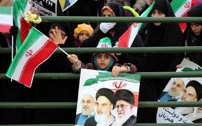 Une jeune fille iranienne tient une affiche avec un portrait du président Hassan Rouhani (à gauche), ledéfunt leader, l'ayatollah Ruhollah Khomeini et l'ayatollah Ali Khamenei, lors des célébrations sur la place Azadi de Téhéran (Place de la Liberté) pour marquer le 37e anniversaire de la révolution islamique le 11 février 2016 (Crédit : AFP / ATTA KENARE)