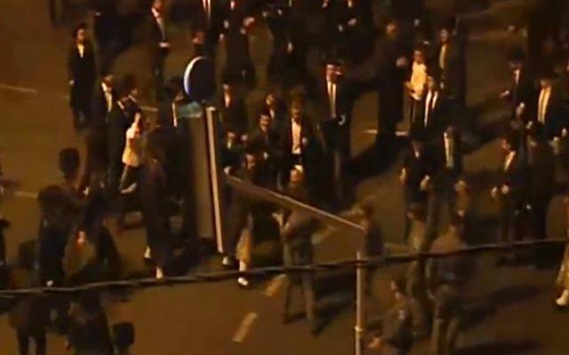 Des hommes ultra-orthodoxes affrontent la police pendant une manifestation contre l'ouverture pendant Shabbat du cinéma Yes Planet, à Jérusalem, le 14 août 2015. (Crédit : capture d'écran Deuxième chaîne)
