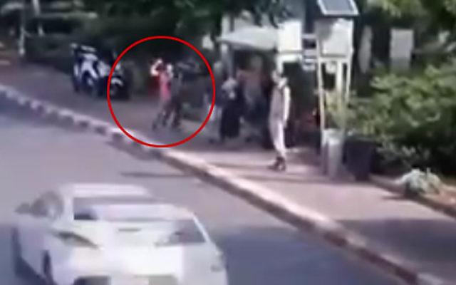 Image d'une caméra de sécurité montrant un terroriste brandissant un couteau (encerclé) et poignardant des Israéliens qui attendent à un arrêt de bus sur le boulevard de Jérusalem à Raanana, le 12 octobre 2015. (Crédit : capture d'écran)