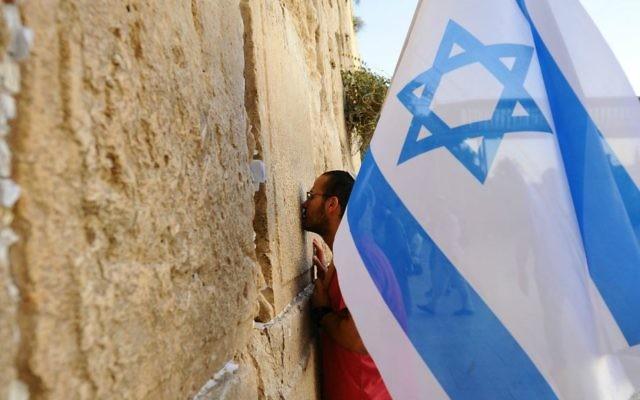 Un homme tient un drapeau israélien au cours d'une marche de soutien à la ville de Jérusalem au mur Occidental le 22 octobre, 2015, après une vague d'attaques terroristes  (Crédit photo: Mendy Hechtman / Flash90)